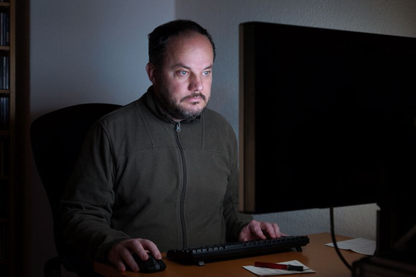 33520108 - middle aged man sitting in front of computer screen in the dark